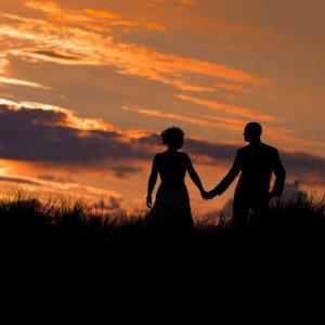 Silhouet van een bruidspaar in de duinen van Ameland.