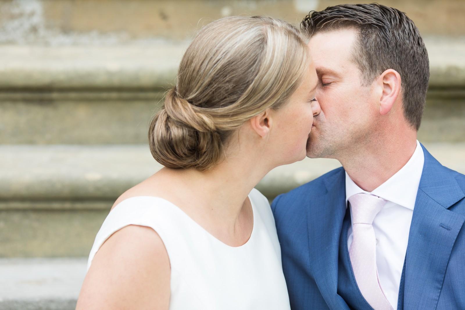 Kus van bruid en bruidegom zittend op een trap