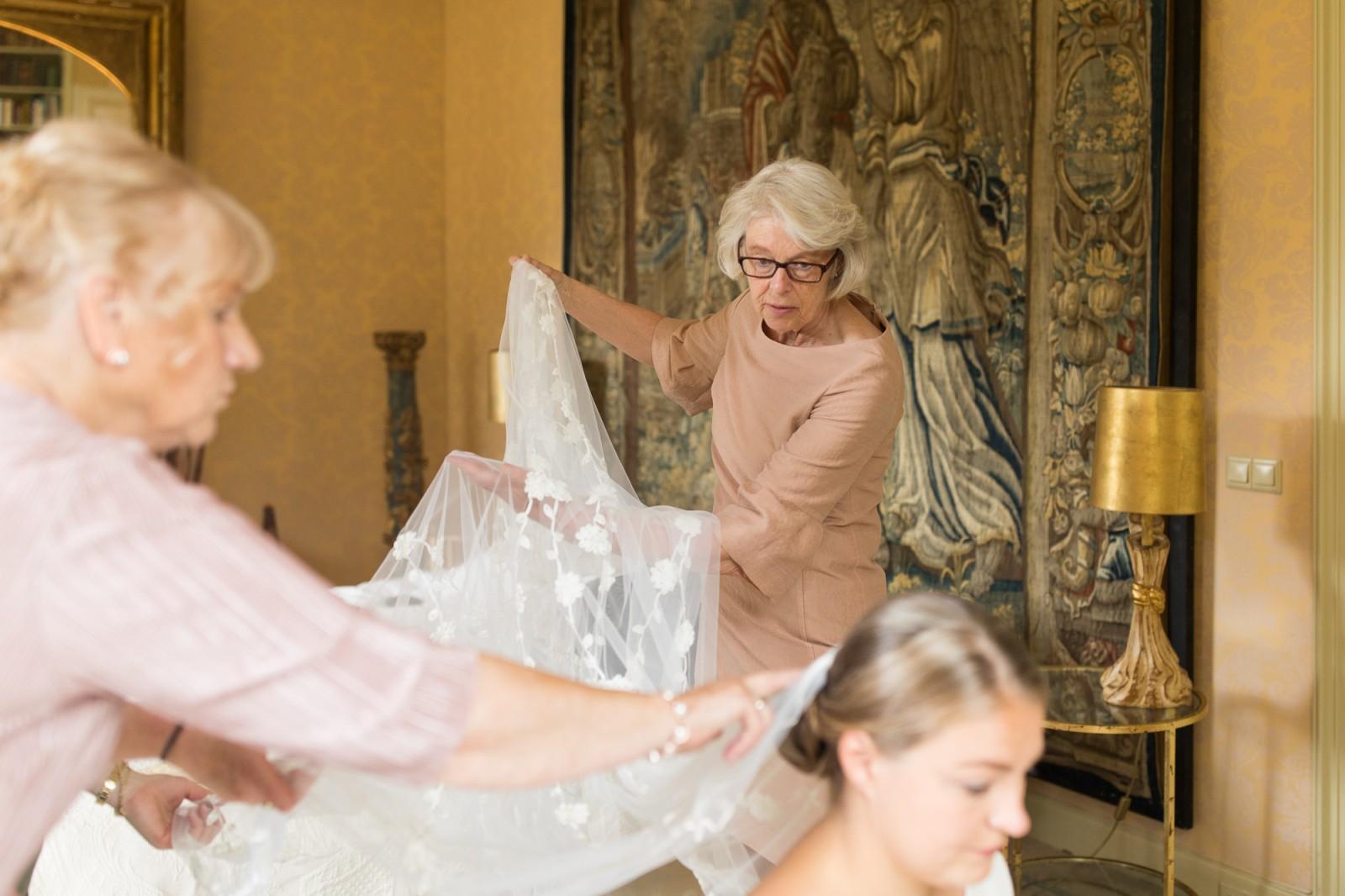 Moeder van de bruid doet de sluier op