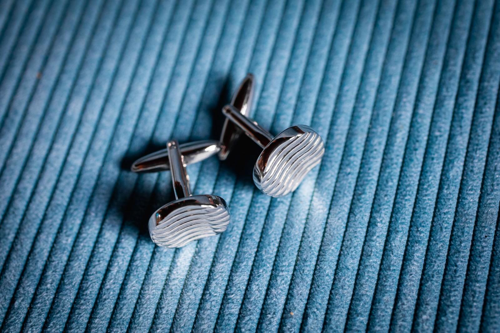 Manchetknopen op een blauwe ondergrond